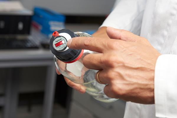 Hands holding bottle with Stay Safe cap