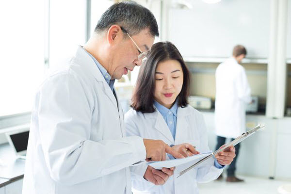 Two lab people looking at a document