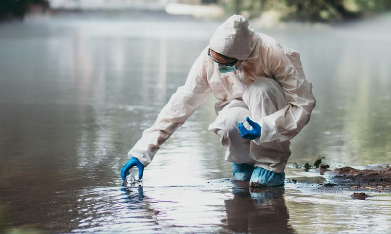 person in protective suit collecting water for testing